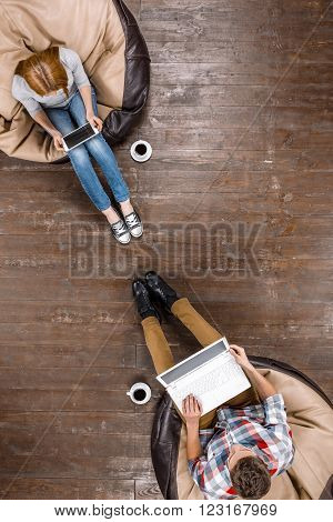 Top view creative photo of beautiful young couple on vintage brown wooden floor. Couple sitting on soft frameless seats and using electronic gadgets