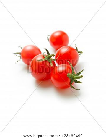 Fresh ripe cherry tomatoes scattered isolated on a white background