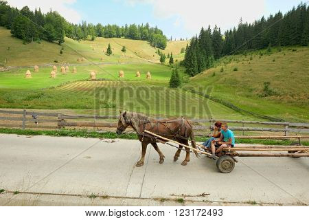 GARDA DE SUS, ROMANIA - AUGUST 04, 2015: a young couple riding a wagon pulled by a horse on a rural road in the Apuseni Mountains