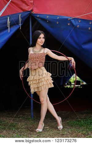 Beautiful girl with hula hoop in designer dress is behind the scenes of the circus. Circus tent
