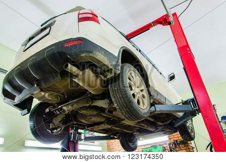 Car on two-post elevator in workshop service station with bottom view
