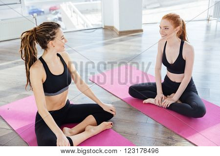 Two smiling sportswomen sitting on pink mats and talking after training