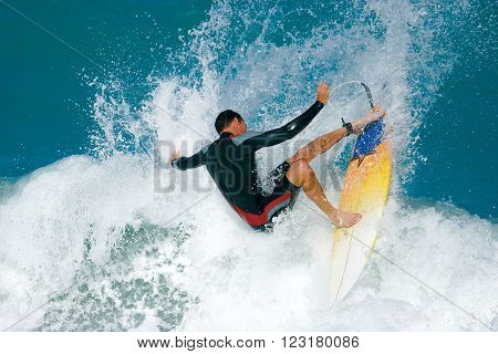 A surfer executes a radical move on a foamy ocean wave.