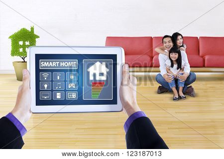Picture of modern applications of smart house system controller on tablet screen. Shot with happy family sitting at home