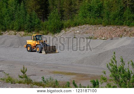 Yellow front loader without a driver at a sand pit.