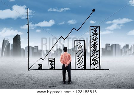 Image of a young businessman looking at a growing chart with upward arrow shot outdoors