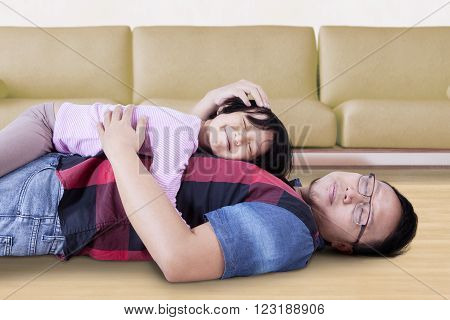 Picture of a young father and his daughter relaxing at home while lying on the floor