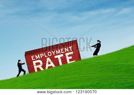 Picture of two young businesspeople moving a block with an employment rate text shot outdoors