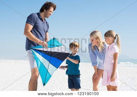 Happy family flying kite at beach. Young small boy flying a kite. Father and son flying the blue kite at beach.