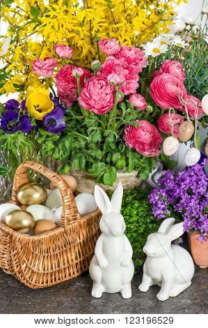Easter decoration with flowers eggs bunnies and cake. Ranunculus campanula forsythia