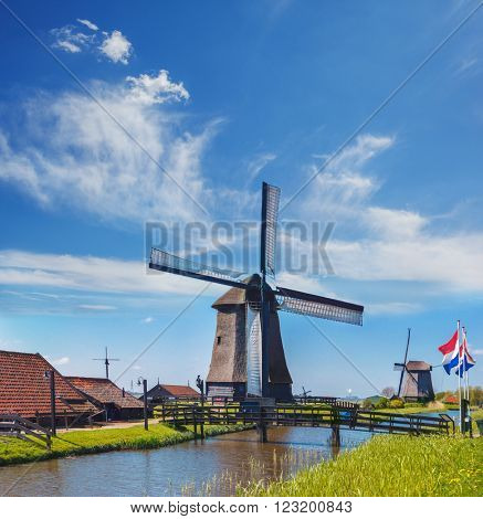 Old mills with Dutch flags standing in front of the bridge over the dyke. Mills are one of the tourists attractions in the Netherlands