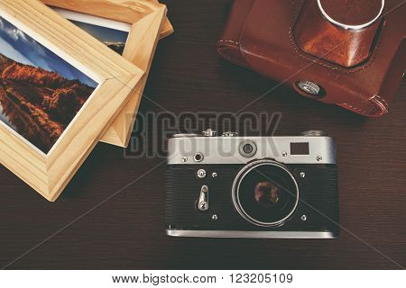 Retro Vintage Camera And Photos In Frame On Wood Background