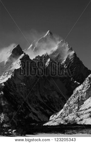 Grand Tetons Peak with snow mist blowing off the top in Grand Teton National Park in Wyoming USA in black and white