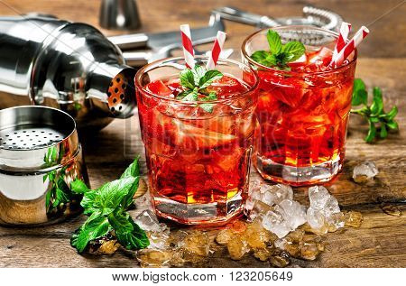 Red drink with strawberry mint leaves ice. Cocktail with campari aperol gin liquor juice soda water