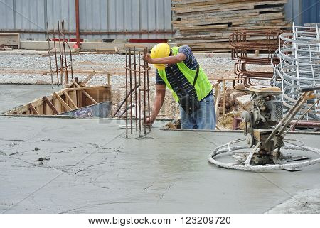 JOHOR, MALAYSIA -OCTOBER 20, 2015: Construction workers levelling the pouring wet concrete on floor at the construction site.