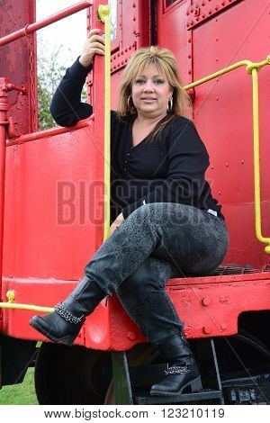 A woman sitting on a caboose waiting for a ride