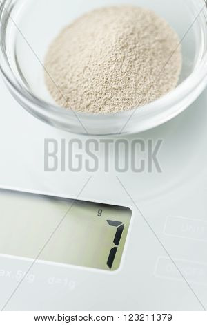 Small portion of dried Yeast (7g) on a scale