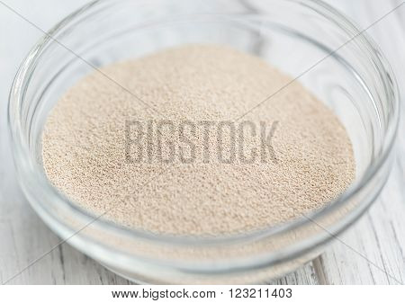 Bowl with dried Yeast (selective focus) on wooden background