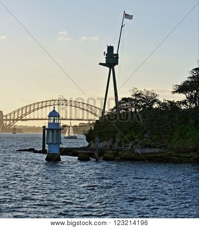 Lighthouse in front of Sydney Harbor Bridge in Sydney at sunset
