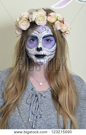 Halloween  blonde girl with makeup Mexican death mask and with a wreath of flowers