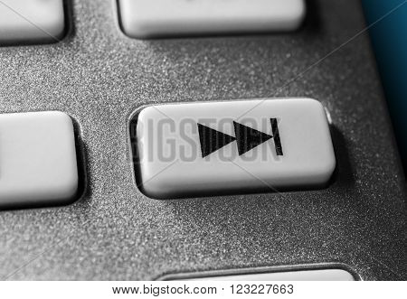 Macro Of A Grey Skip Forward Button On Chrome Remote Control For A Hifi Stereo Audio System