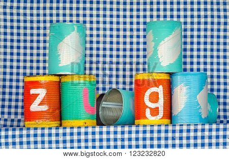 Tin cans for throwing balls at them on blue and white striped background