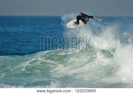 A surfer executes a radical aerial on a blue ocean wave.