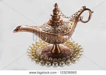 Aladdin's lamp and pearls necklace isolated on white background