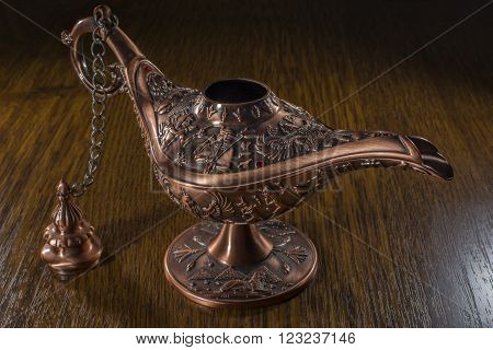 Aladdin's lamp isolated on brown wood background