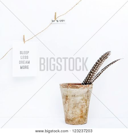 Scandinavian hipster interior design. Vintage pot with quill GARLAND hanging on the wall. Quotes SLEEP LESS DREAM MORE BE HAPPY