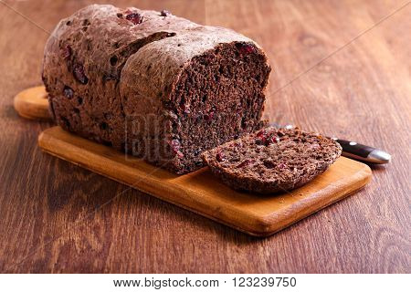 Chocolate bread with dried berries on board