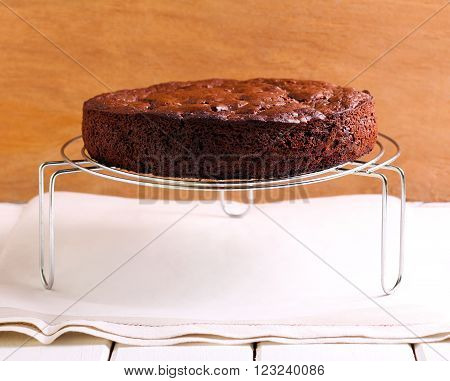 Chocolate sponge cake on rack on table