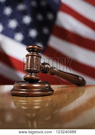 Wooden gavel on glossy table, The flag of USA in the background.
