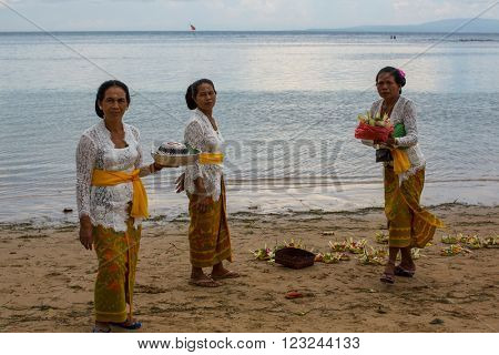 SANUR, BALI - MAR 18, 2016: Unidentified people during Melasti Ritual. Ceremony is held on the edge of the beach with the aim to purify oneself of all the bad things in the past and throw it to ocean.
