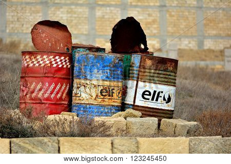 BAKU, AZERBAIJAN - FEBRUARY 10 2014  Three old oil barrels outside of Baku, capital of Azerbaijan. Oil barrels stand discarded in a suburb of Baku, the capital city.  Evidence of the country's petrochemical industry is inescapable