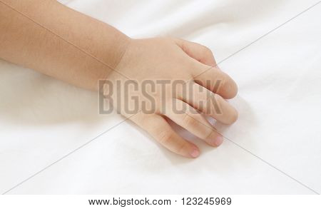 Back hand of asian baby on white bedcovers.