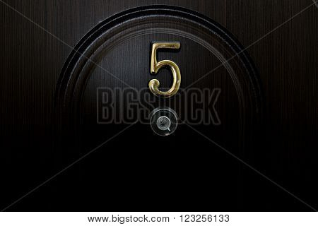 Number five and a peephole on the front door a dark color.