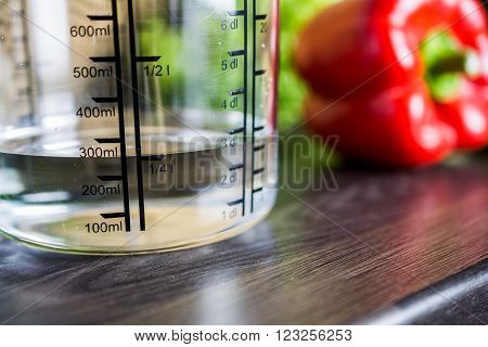 250Ccm / 1/4 Liter / 250Ml Of Water In A Measuring Cup On A Kitchen Counter With Food