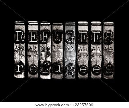 Refugees concept in metal type on black