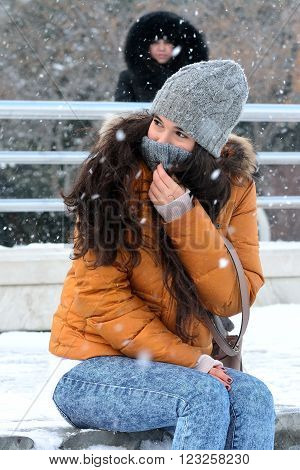 BAKU, AZERBAIJAN - JANUARY 31 2014 Pretty girl covering her face in the snow. An unusual snowfall in Baku is the cause of something of a party atomosphere, with many people playing and posing for photographs on the Bulvar, on the coast of the Caspian Sea