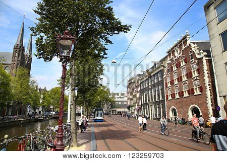AMSTERDAM; THE NETHERLANDS - AUGUST 19; 2015: View of Singel street and De Krijtberg church from Koningsplein. Street life canal pedestrians tram and bicycle Amsterdam is capital of the Netherlands on August 19; 2015.