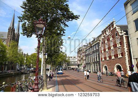 AMSTERDAM; THE NETHERLANDS - AUGUST 19; 2015: View of Singel street and De Krijtberg church from Koningsplein. Street life canal pedestrians tram and bicycle Amsterdam is capital of the Netherlands on August 19; 2015.