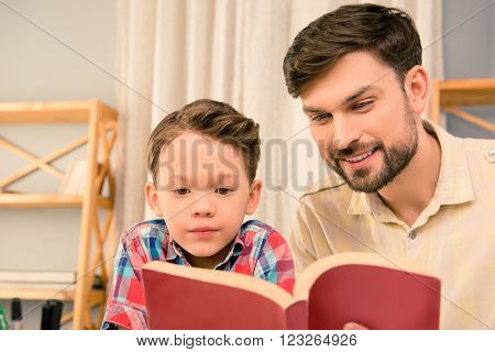 Close Up Portrait Of Handsome  Father Reading Book To His Son