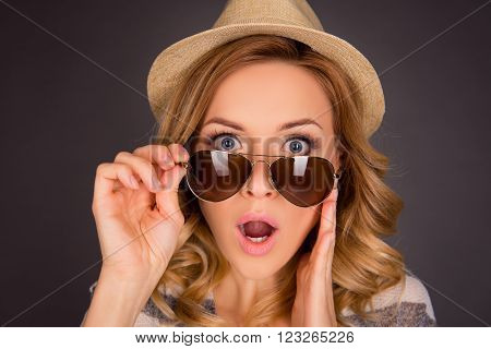 Close up portrait of shocked young woman  touching her spectacles