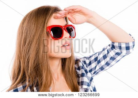 Close up portrait of attractive young woman in red spectakles looking for way