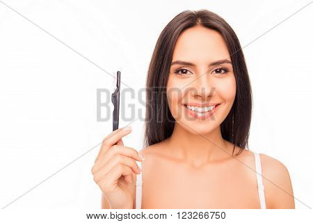 Cheerful Young Brunette Holding Brash Of Mascara On White Background