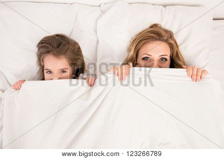 Top View Of Comic Woman And Her Daughter Hiding Faces Behind Blanket
