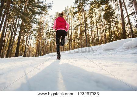 The sport girl running in winter Park