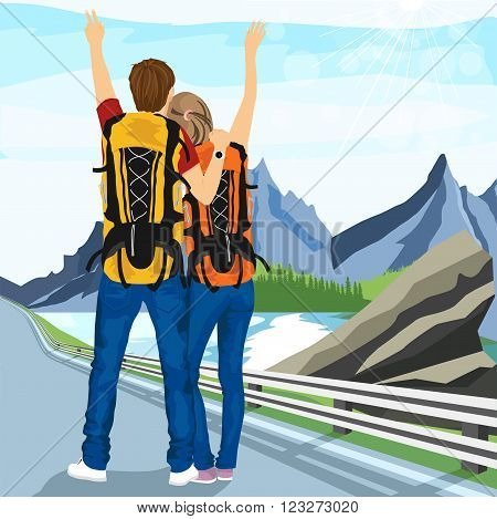 rear view of young couple of hitchhikers standing on road and enjoying mountain scenery