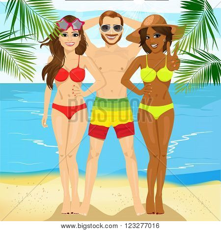 macho man standing with two attractive women on tropical beach and one of them showing victory sign